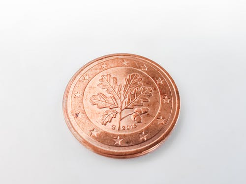 Gold Round Coin on White Surface