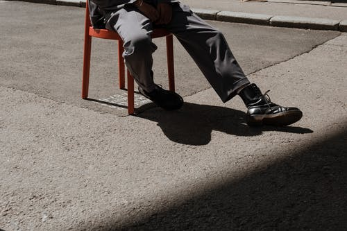 Person in Black Pants and Black Shoes Sitting on Red Chair