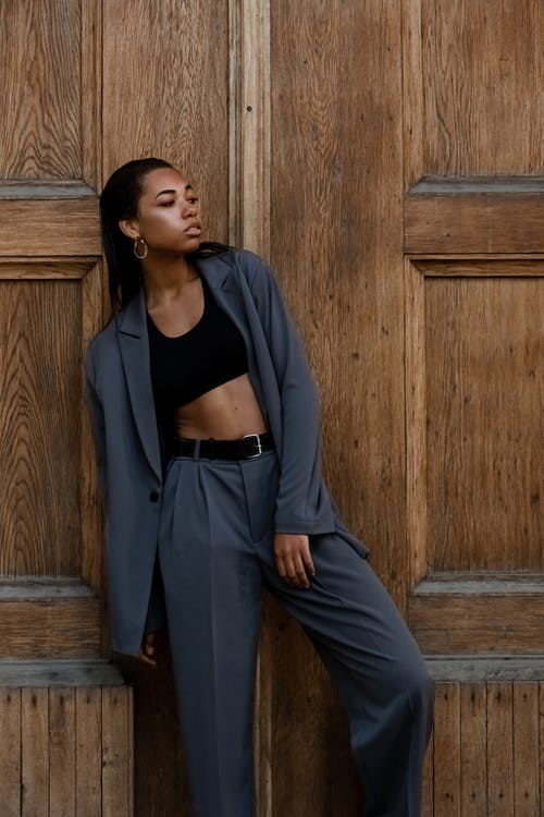 Woman in Black Long Sleeve Shirt and Blue Pants Standing Beside Brown Wooden Wall