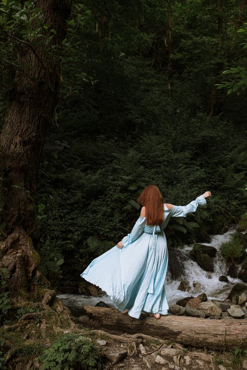 Back View of a Woman Standing Barefoot on Fallen Tree Trunk