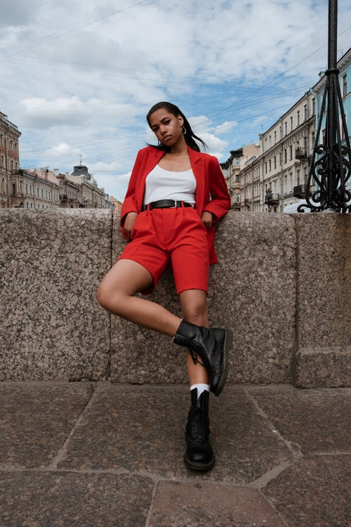 Woman in Red and White Long Sleeve Shirt and Red Shorts Sitting on Gray Concrete Wall