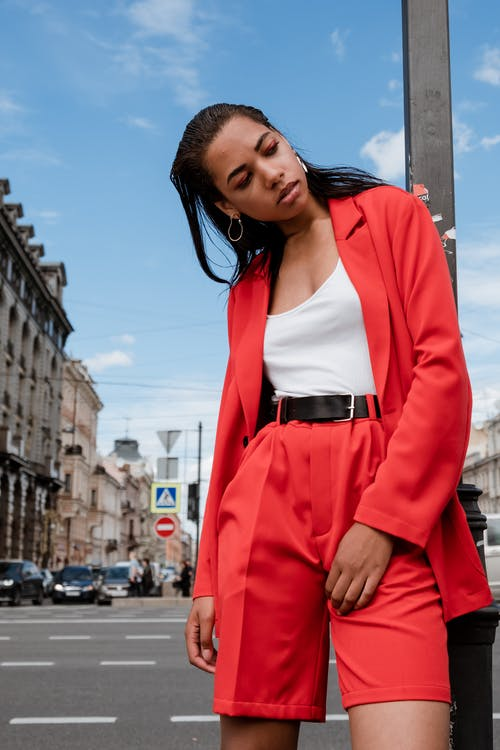 Woman in Red Blazer Standing Near Building