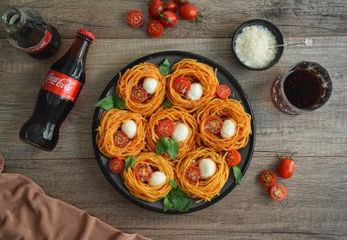 Appetizing spaghetti nests with cheese near bottles of coke