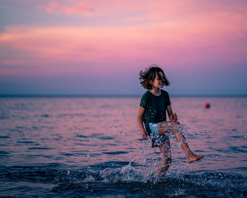 Glad girl jumping in water of sea