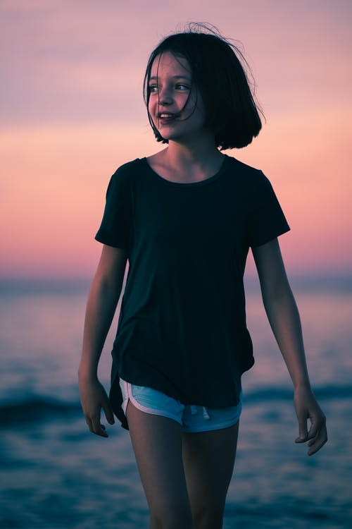 Glad little girl with toothy smile looking away and walking on sandy beach during rest