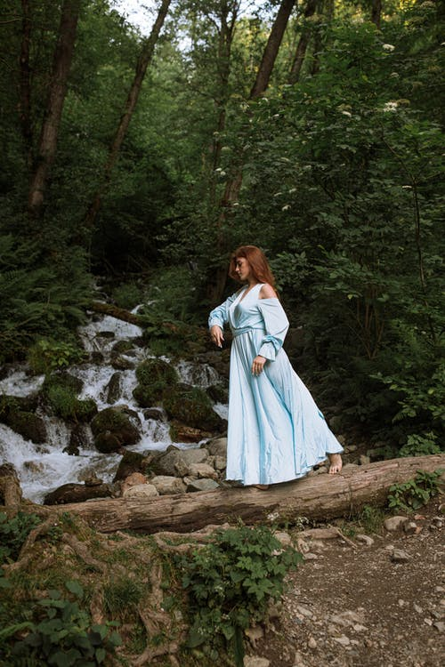 Woman in White Dress Standing on Rocky Ground Surrounded by Trees