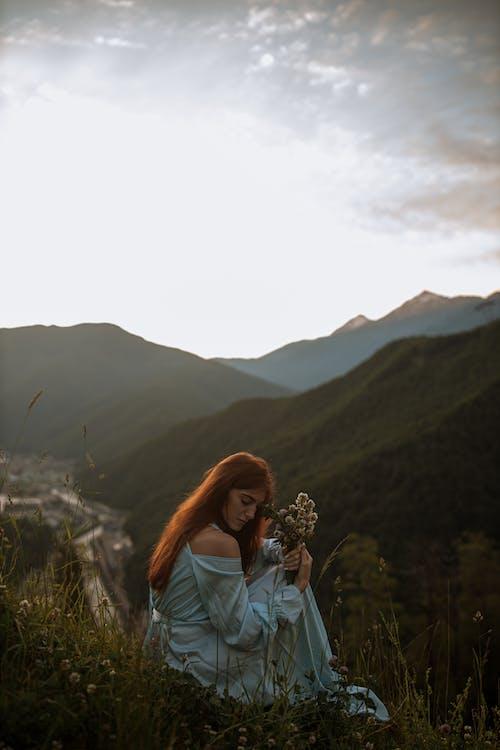 Woman in Blue Denim Jacket Standing on Green Grass Field