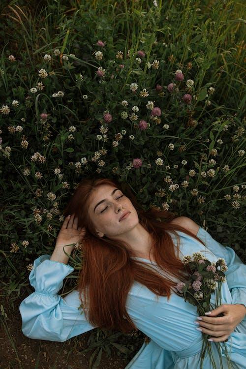 Woman in Blue Dress Lying on Green Grass