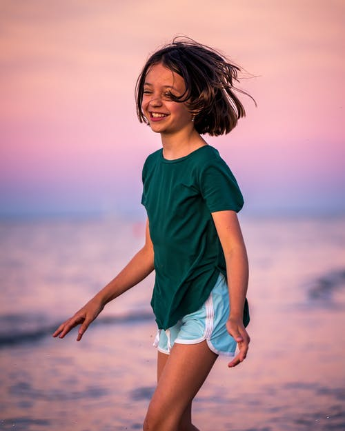 Cheerful little girl wearing casual clothes with toothy smile and closed eyes standing in sea