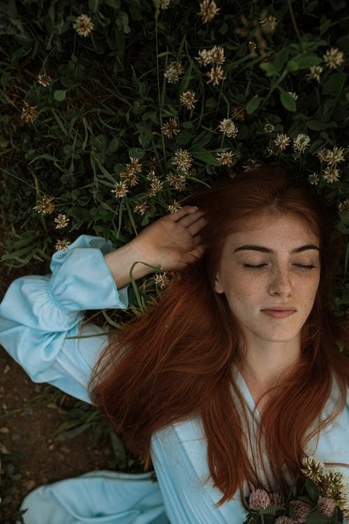Woman in White Long Sleeve Shirt Lying on Green Grass