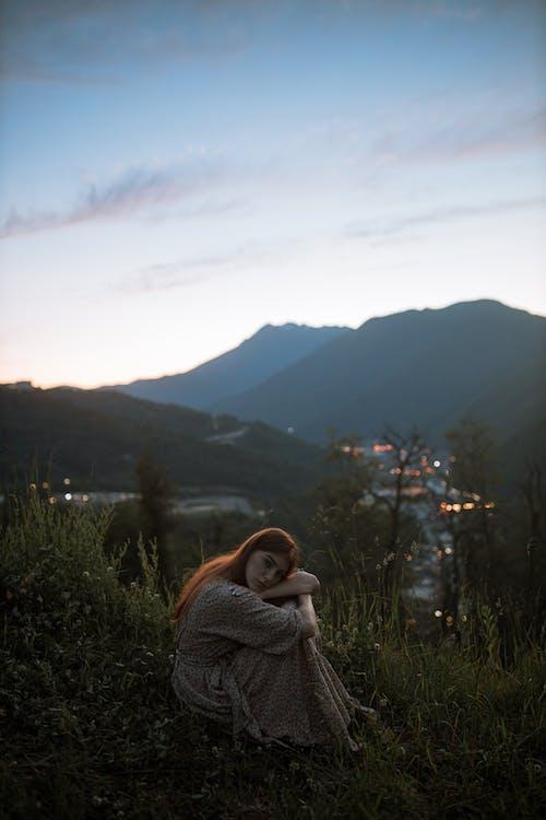 Woman in Gray Sweater Sitting on Green Grass Field