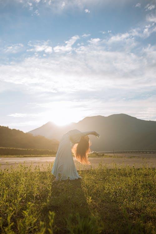 Woman in White Wedding Dress Standing on Green Grass Field