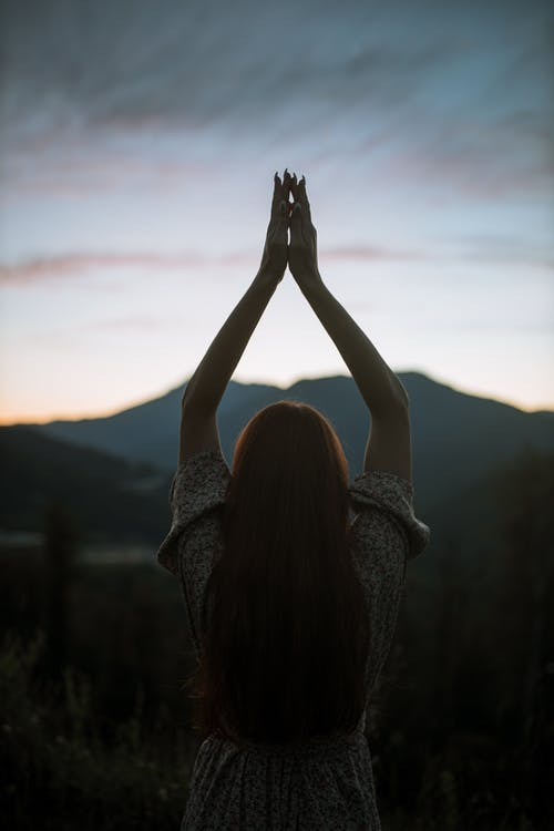 Woman in Gray Knit Sweater Raising Her Hands