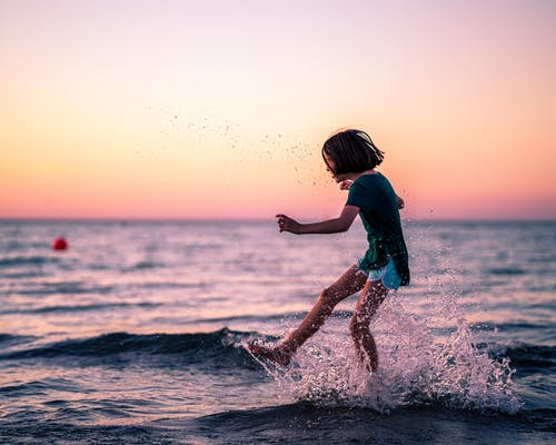 Side view of little girl playing with water in sea while having free time in summer evening