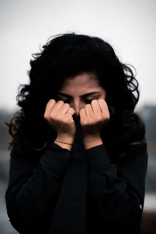 Woman in Black Jacket Covering Her Face