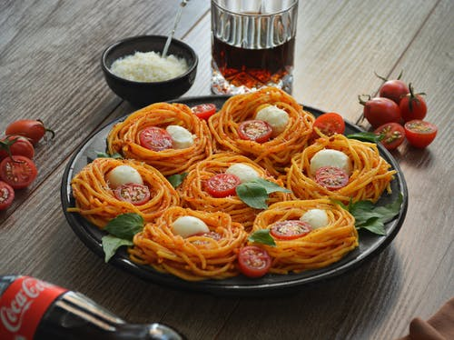 From above of tasty spaghetti with cherry tomato slices and mozzarella near bowl with grated parmesan on wooden table