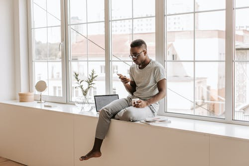 Man in Gray Crew Neck T-shirt and Gray Pants Sitting on White Wooden Window