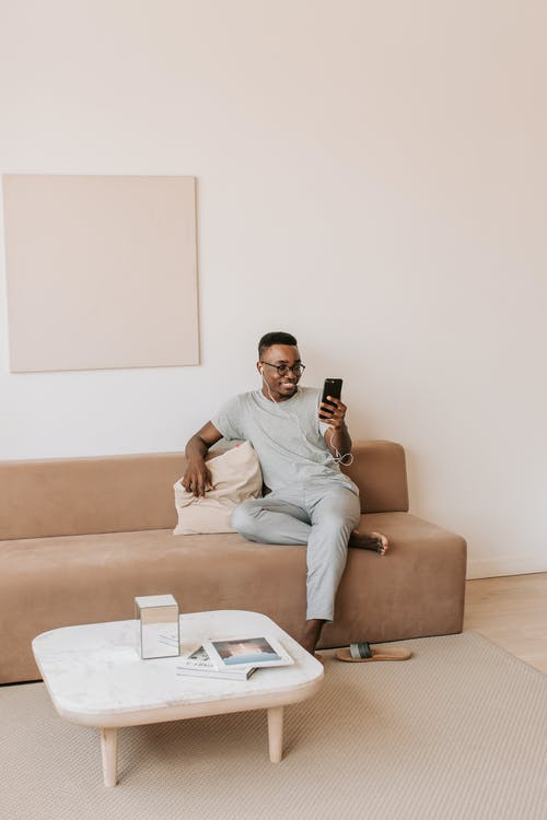 Man in White Crew Neck T-shirt Sitting on Brown Sofa
