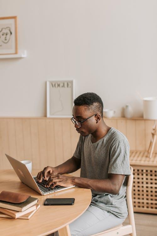 Man in Gray T-shirt Typing on Laptop