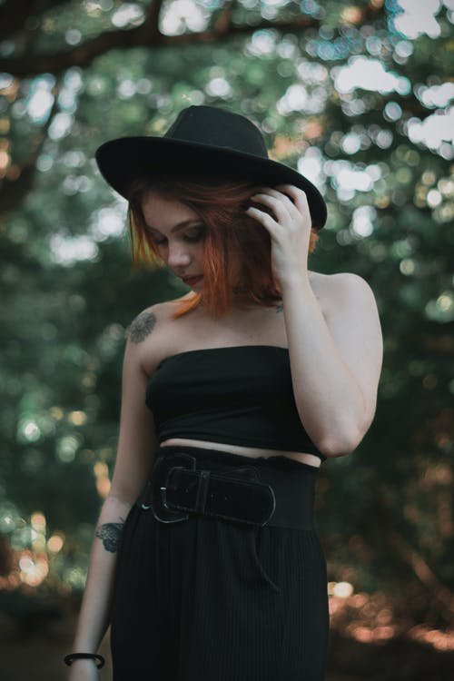 Stylish young lady touching hair while standing near green trees