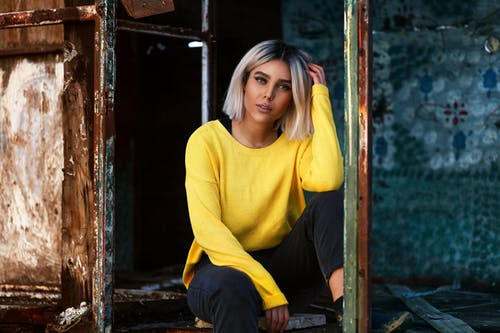 Woman in Yellow Sweater Sitting on Brown Wooden Chair