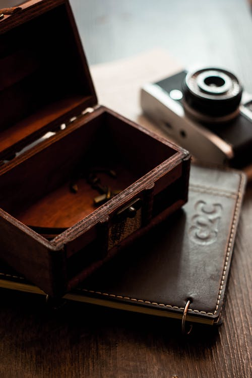 From above of vintage wooden box and leather notebook placed on table with retro film camera