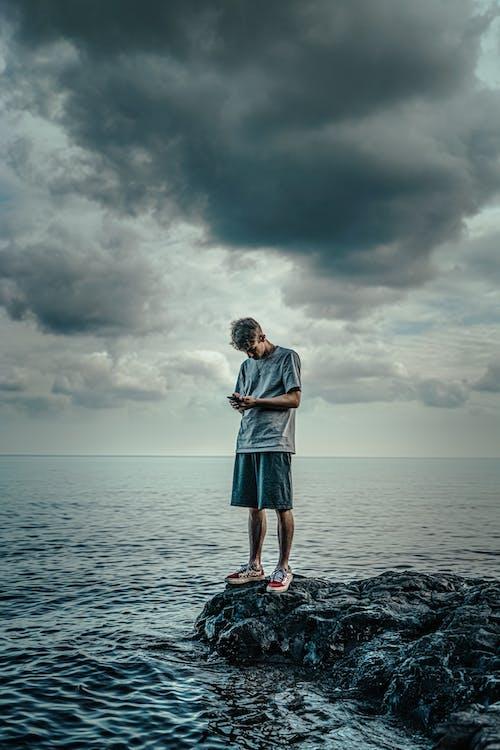 海の前の岩の上に立っている白い長袖シャツと青いスカートの女性