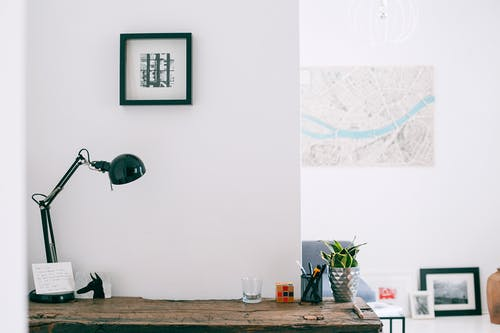 Lamp with cup of stationery placed on wooden desk with potted plant in light cozy apartment