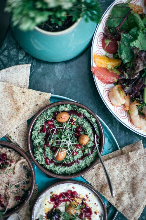Appetizing assorted hummus served with mixed salad in cafe