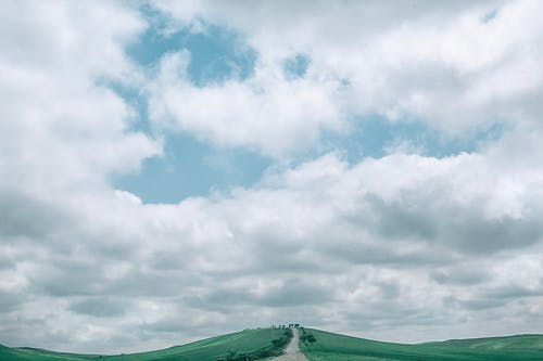 Picturesque scenery of fluffy cumulus clouds floating in blue sky over narrow road going through grassy mountainous terrain