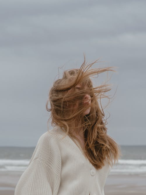 Side view of pensive young female traveler with long wavy hair in stylish knitted cardigan relaxing on beach of waving ocean against overcast sky on windy day