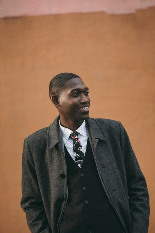 Confident young African American male model in elegant suit and coat standing against brown wall with hands in pockets and looking away