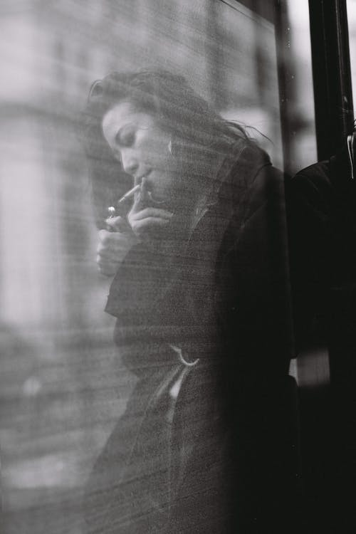 Pensive young ethnic lady smoking cigarette near glass wall on street