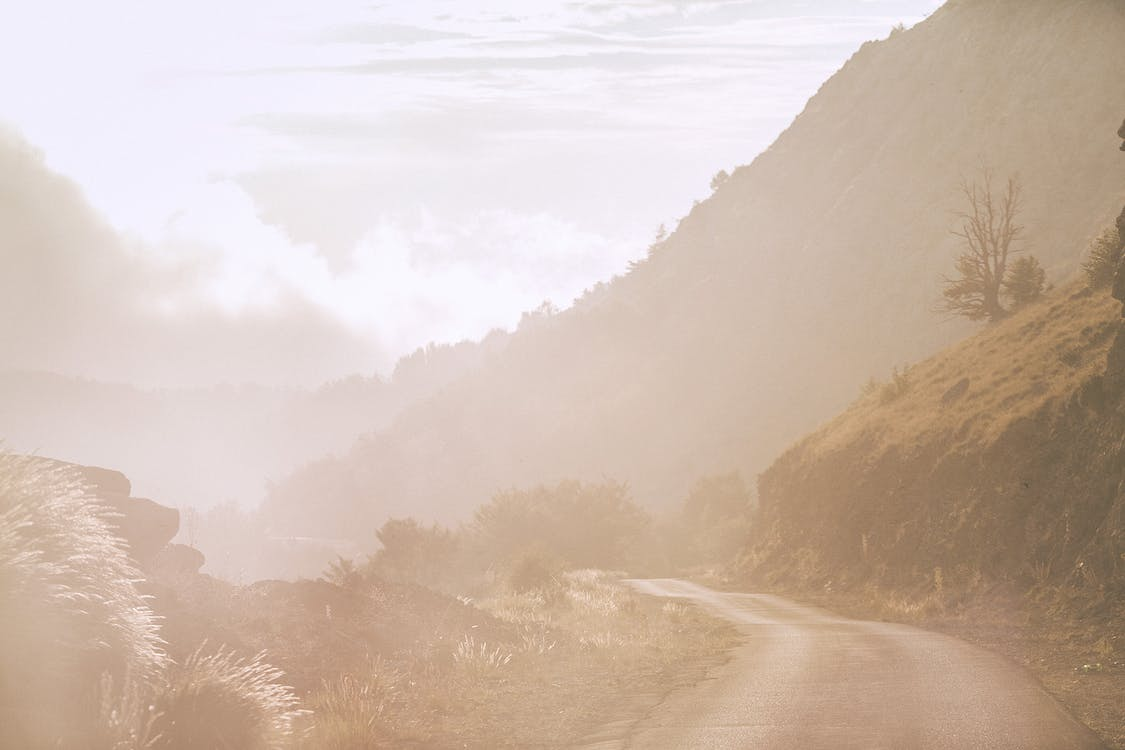 Spectacular scenery of narrow rural road going through rocky hills in mountainous valley on foggy day