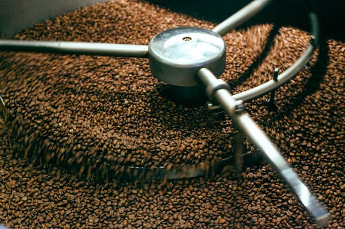 From above of fresh aromatic brown coffee beans mixing in professional roasting machine