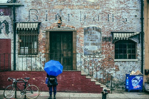 Back view of unrecognizable traveler in warm clothes in backpack and umbrella in hand standing on street near aged historical brick building during sightseeing tour in city