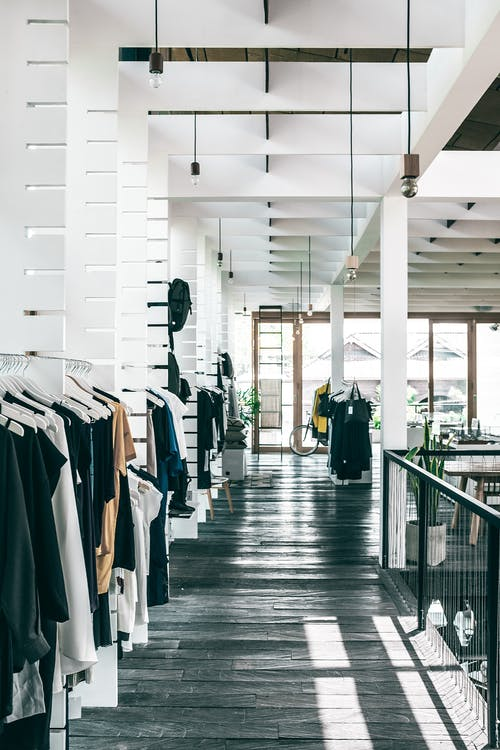 Interior of spacious modern fashion boutique with collection of various clothes hanging on racks in sunlight