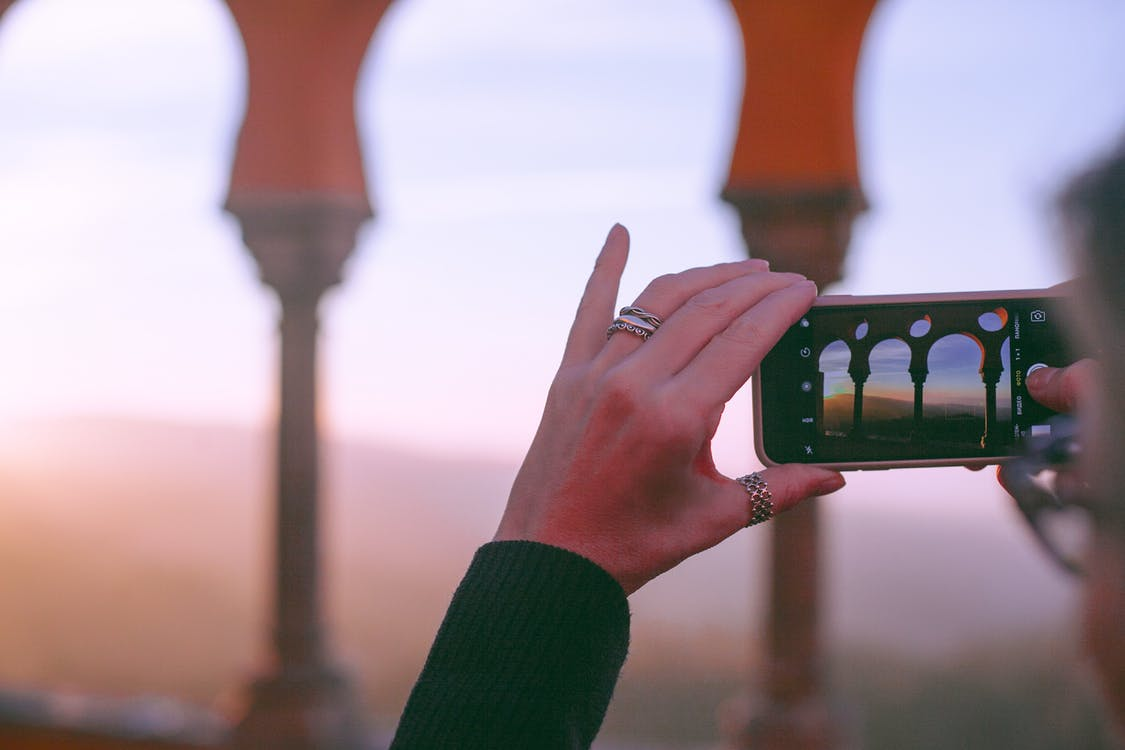 Crop unrecognizable female traveler taking photo of old oriental castle with arched passage on mobile phone against sunset sky