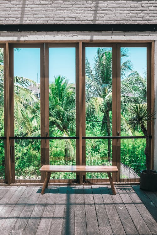 Wooden chair placed in spacious villa near panoramic windows overlooking lush green tropical garden against cloudless blue sky