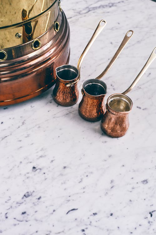From above set of copper cezves placed on marble table near authentic sand brazier before oriental coffee preparation