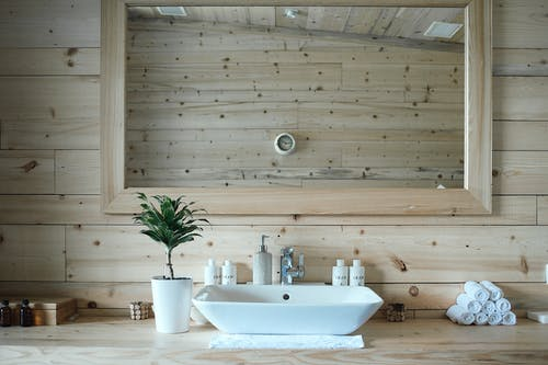 Stylish interior design of contemporary bathroom with wooden walls and big mirror above sink and table with toiletries