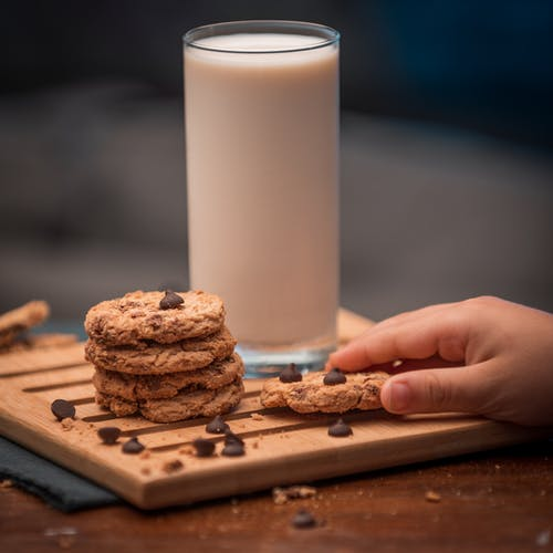 Person Holding Brown Cookies Beside White Pillar Candle