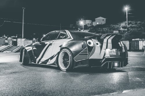 Black and white of contemporary sports auto on asphalt roadway near shiny lamp posts in evening