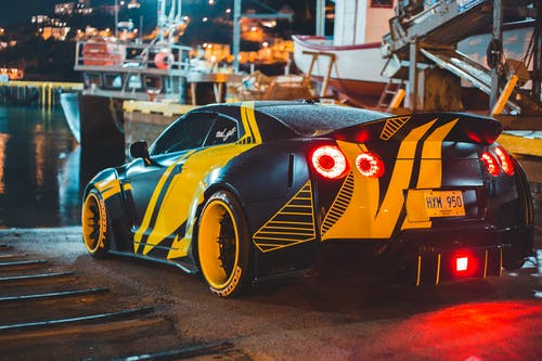 Contemporary sports car with glowing taillights near river with ships in city harbor in evening