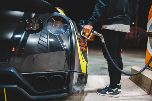 Side view of crop unrecognizable male refueling modern racing automobile in petrol station in evening