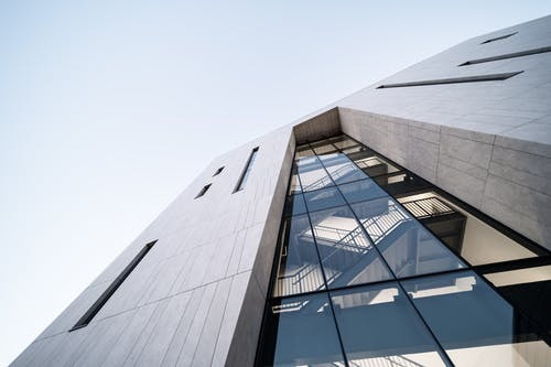 Modern building facade with stairs inside under sky