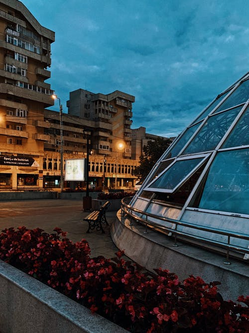Modern city street with concrete residential building and unusual glass construction in spherical shape in twilight
