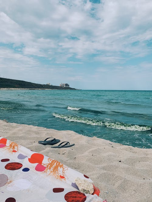 Amazing view of turquoise sea waving over sandy shore with flip flops and colorful beach towel on warm summer day