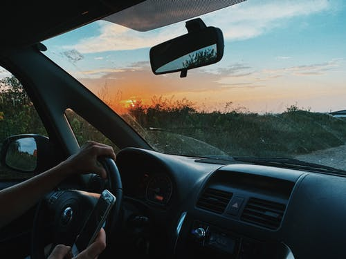 Crop unrecognizable person browsing mobile phone and driving car along rural gravel road in sunset time
