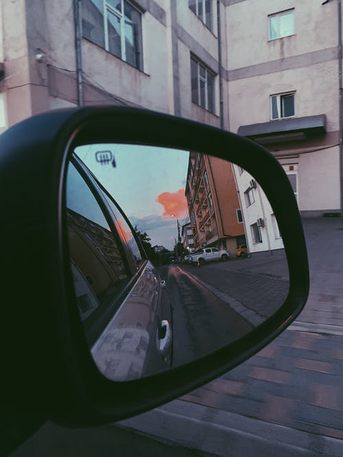 Vibrant sunset and row of constructions reflecting from automobile mirror of car parked in yard of residential building